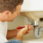 man tightening sink
